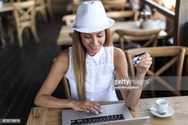 Cheerful young woman drinking coffee and using credit card