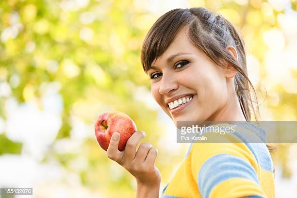 Cheerful young woman eating an apple