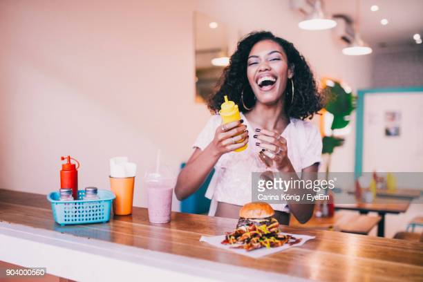 Cheerful Young Woman Eating Burger At Cafe