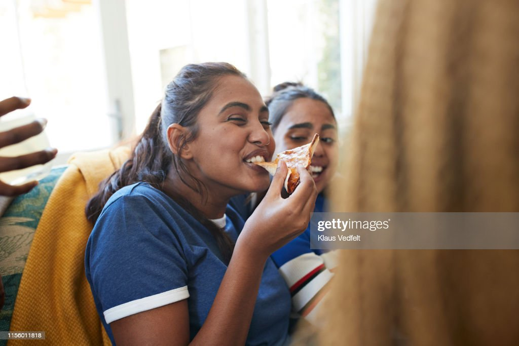 Cheerful young woman eating slice of pizza : Stock Photo