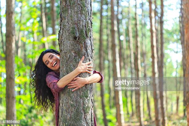 cheerful young woman embracing a tree in the forest - tree hugging stock pictures, royalty-free photos & images