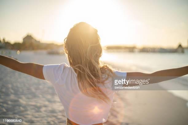 fröhliche junge frau umarmt die natur bei sonnenuntergang; hündin steht auf strandarmen ausgestreckt - spirituality stock-fotos und bilder
