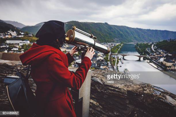 Cheerful young woman enjoying sightseeing telescope against Cochem town in Germany