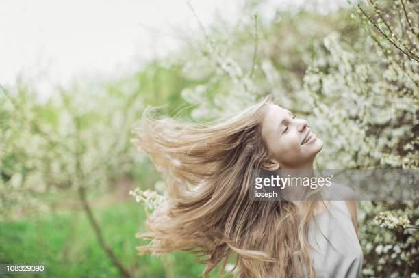 Fröhliche junge Frau, die im Freien Frühling