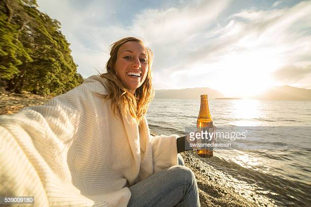 Cheerful young woman enjoys a drink by the lake shore