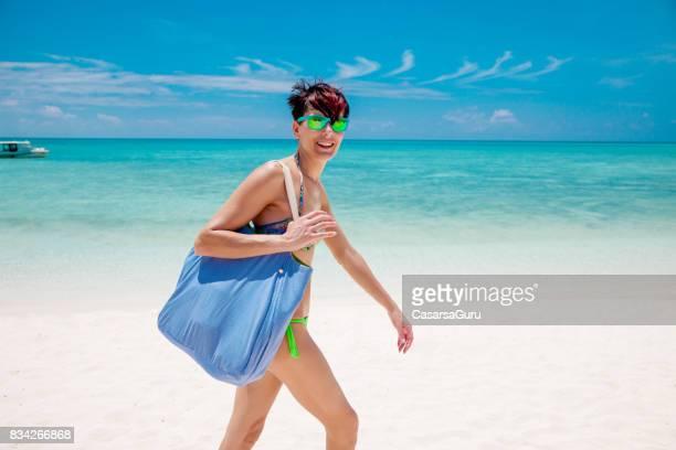 bonne humeur jeune femme va sur la plage - sac porté épaule photos et images de collection