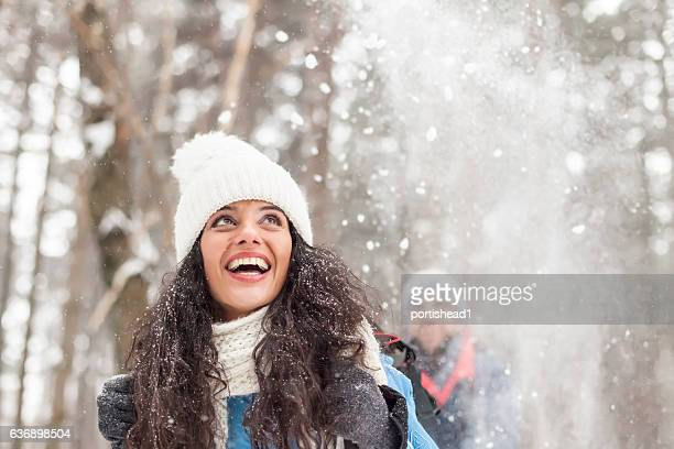 Cheerful young woman having fun in the snow forest