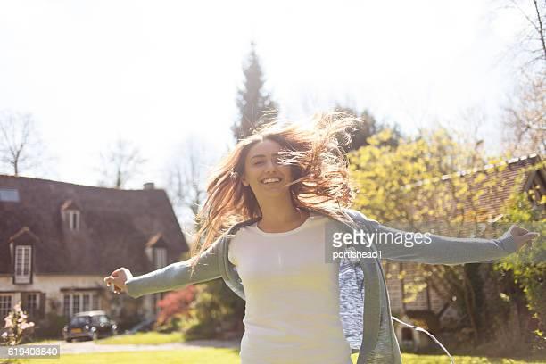 Cheerful young woman having fun on back yard