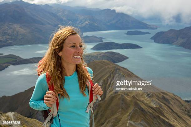 Cheerful young woman hiking above lake, New Zealand