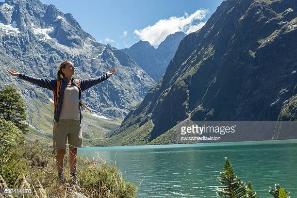 Cheerful young woman hiking reaches mountain lake, arms outstretched
