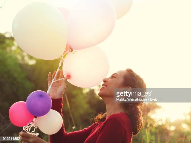 Cheerful Young Woman Holding Balloons While Standing Against Sky