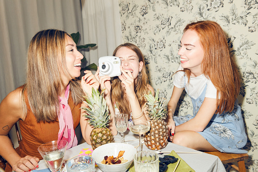 Cheerful young woman holding camera while sitting amidst female friends at home during dinner party - gettyimageskorea