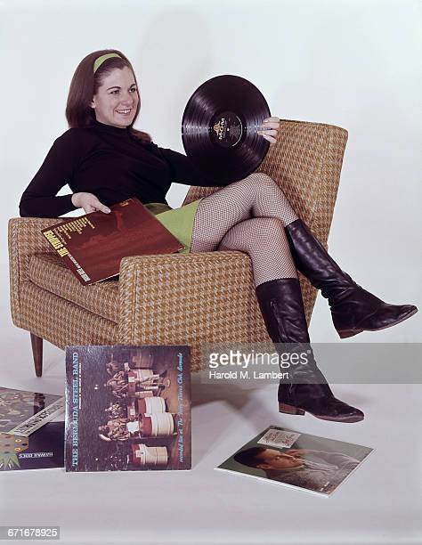 cheerful young woman holding disc and cover while sitting on arm chair  - {{ contactusnotification.cta }} stock pictures, royalty-free photos & images