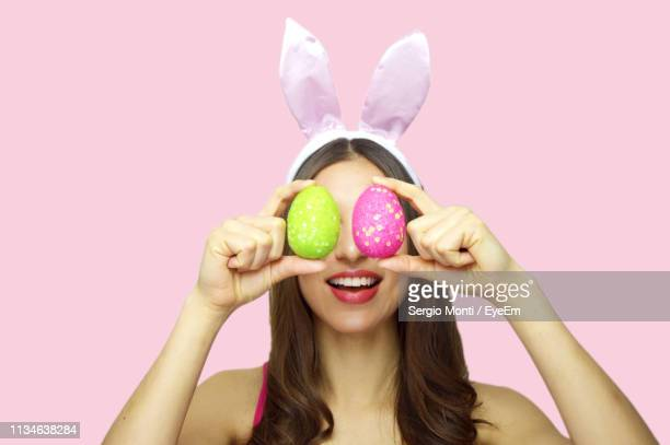 cheerful young woman holding easter eggs against pink background - easter egg stock pictures, royalty-free photos & images