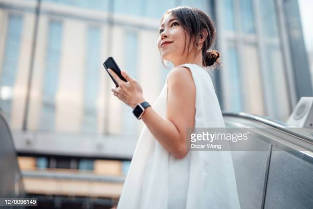 cheerful young woman holding mobile phone on escalator - airport stock pictures, royalty-free photos & images