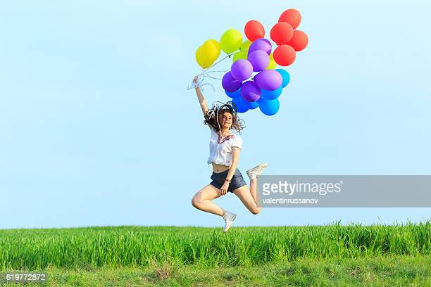 Cheerful young woman holding multicolored balloons jumping