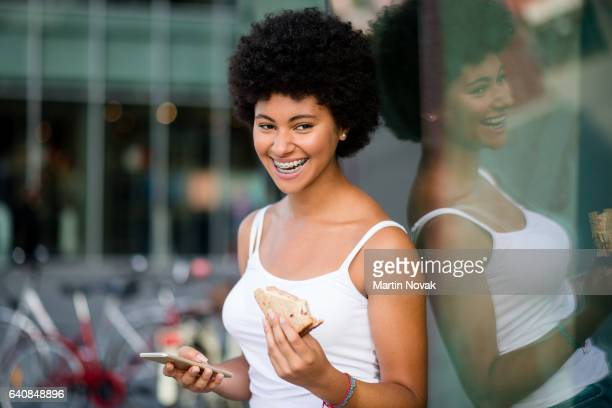 Cheerful young woman holding sandwich and smartphone