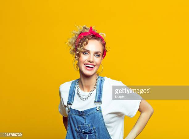cheerful young woman in 80's style outfit, portrait on yellow background - bib overalls stock pictures, royalty-free photos & images