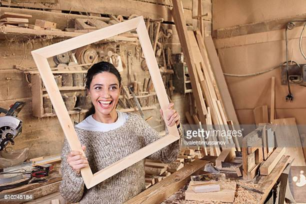 Cheerful young woman in carpenter workshop looking through frame
