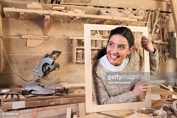 Fröhliche junge Frau in carpenter-workshop