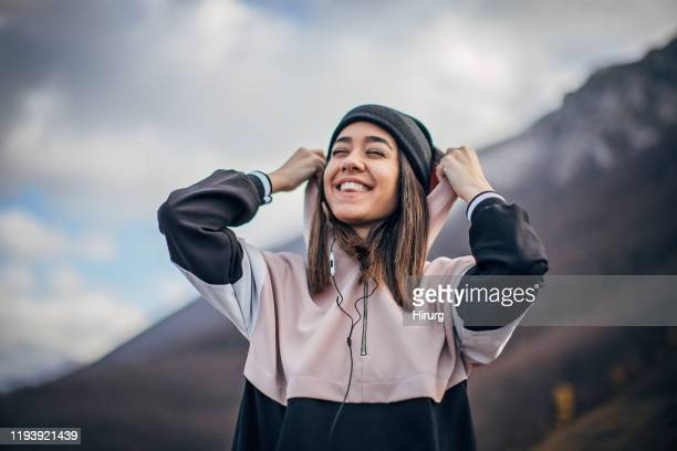 cheerful young woman in sports clothing is listening to music - knit hat stock pictures, royalty-free photos & images
