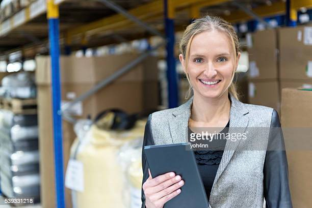 Cheerful young woman in warehouse holding tablet