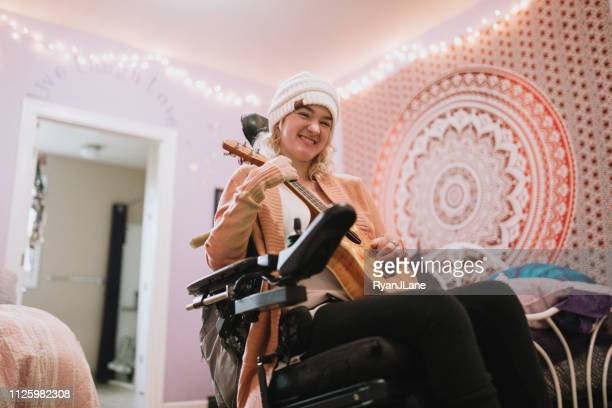 cheerful young woman in wheelchair at home with ukulele - physical disability stock pictures, royalty-free photos & images