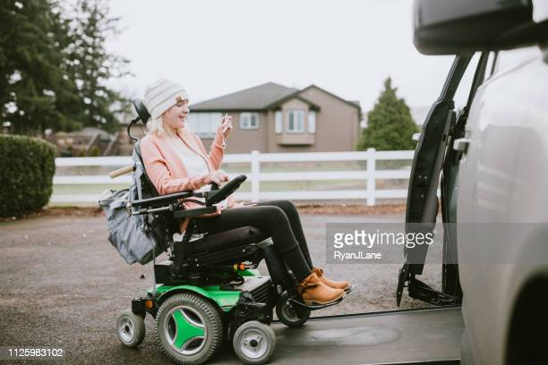 cheerful young woman in wheelchair entering vehicle - accessibility stock pictures, royalty-free photos & images
