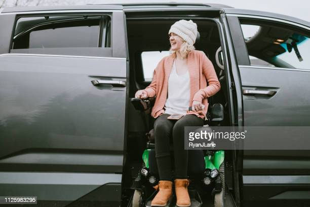 cheerful young woman in wheelchair entering vehicle - mode of transport stock pictures, royalty-free photos & images