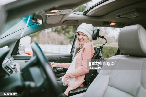 cheerful young woman in wheelchair entering vehicle - assistive technology stock photos and pictures