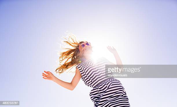 Cheerful young woman jumping on sunny day
