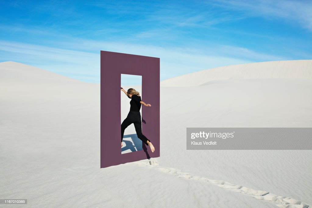 Cheerful young woman jumping through door frame at desert : Stock-Foto