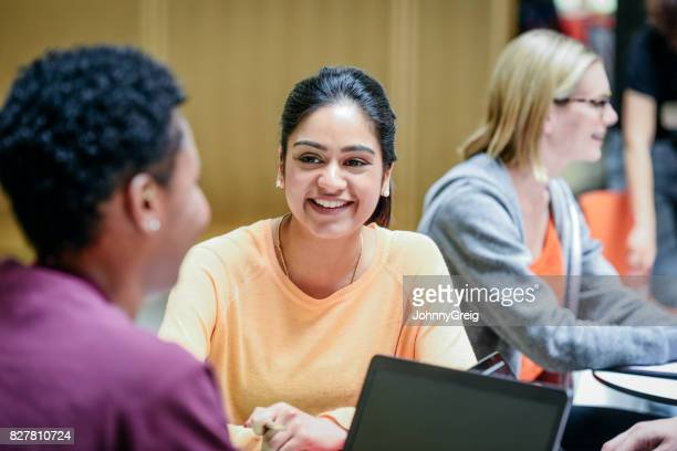 Cheerful young woman listening to friend in college classroom, smiling