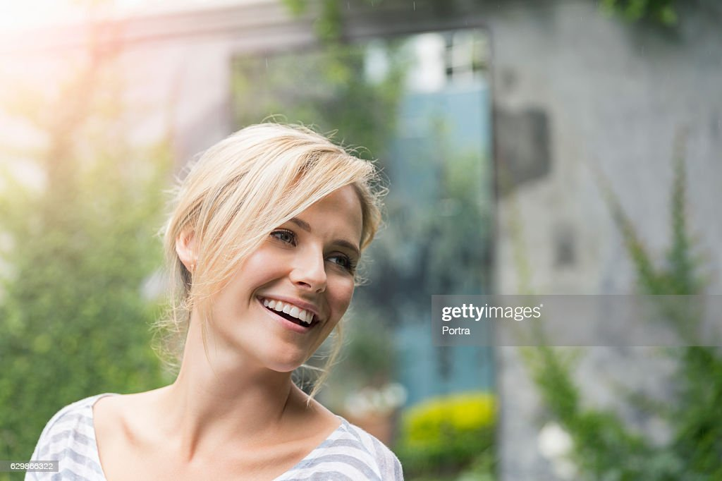 Cheerful young woman looking away at yard : Stockfoto