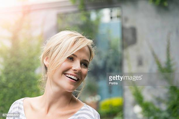 cheerful young woman looking away at yard - mid adult stock-fotos und bilder