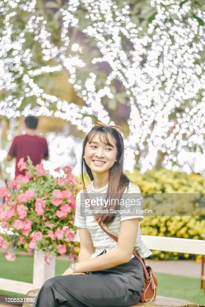cheerful young woman looking away while sitting on bench against illuminated lights at park - pattanasit stock pictures, royalty-free photos & images