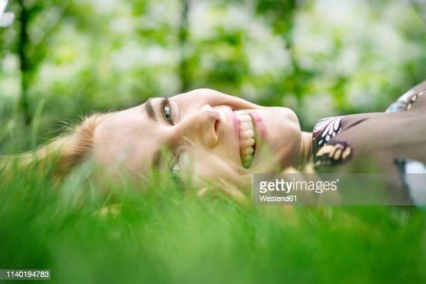 cheerful young woman lying on grass, relaxing - liegen stock-fotos und bilder