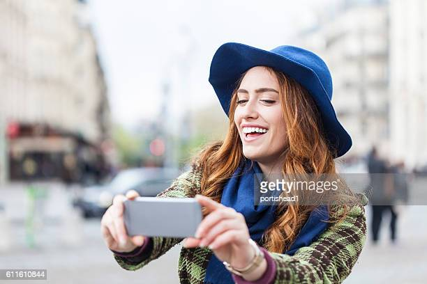 Cheerful young woman making selfie on street