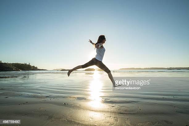 Alegre mujer joven en la playa saltos de alegría y la libertad