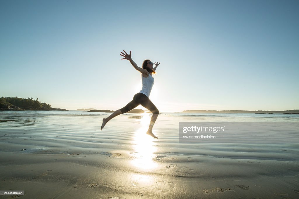 Cheerful young woman on beach jumping for joy and freedom : Stock Photo
