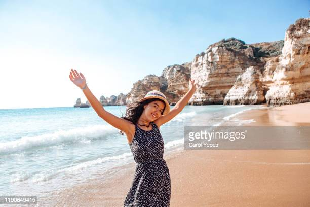 cheerful young woman open arms in rocky beach,algarve,portugal - ポルトガル ファロ県 ストックフォトと画像