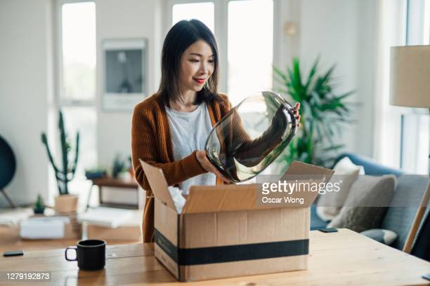 cheerful young woman opening a delivery box at home - receiving stock pictures, royalty-free photos & images
