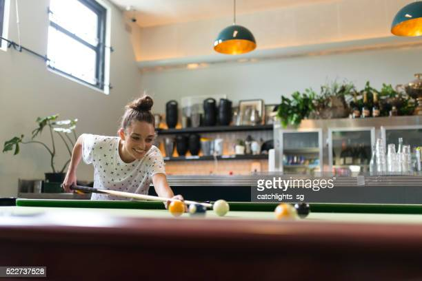 Cheerful Young Woman Playing Pool in a Bar