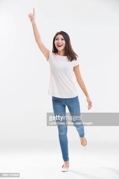 cheerful young woman pointing - 半そで ストックフォトと画像
