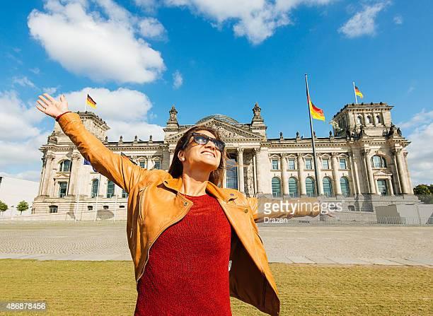 Fröhliche junge Frau setzen Arme nahe Bundestag nach Berlin, Deutschland