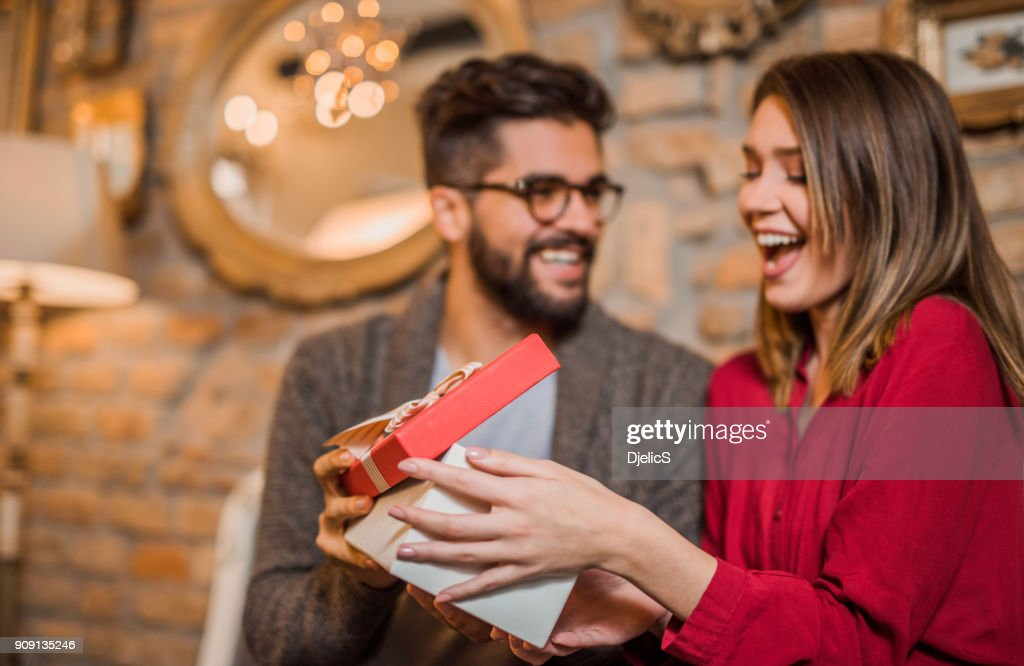 Cheerful young woman receiving a gift from her boyfriend. : Stock Photo