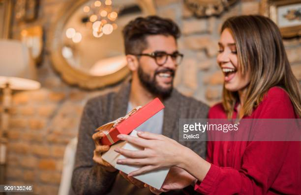 cheerful young woman receiving a gift from her boyfriend. - valentine's day holiday stock pictures, royalty-free photos & images