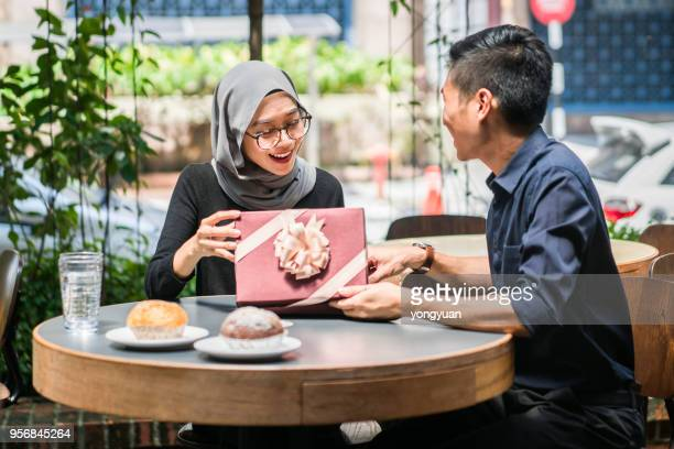 cheerful young woman receiving a gift from her boyfriend - muslim couple stock pictures, royalty-free photos & images