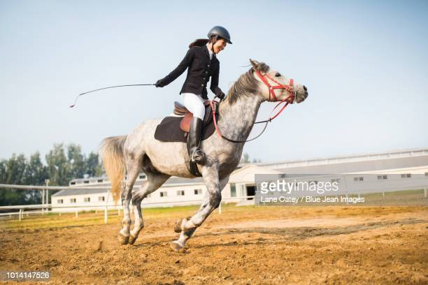 cheerful young woman riding horse - riding boot stock pictures, royalty-free photos & images