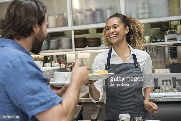 Cheerful young woman serving male customer in cafe